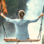 A woman balances on a swing in front of a waterfall, illustrating how the prayer of the heart brings life into balance.